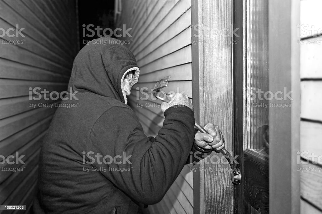 Thief breaking into Home with Crowbar - black and white stock photo