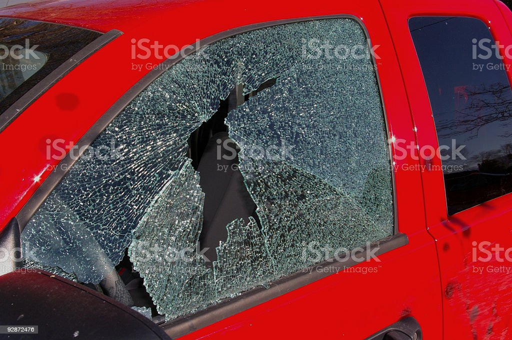 Thief: broken window on the drives side of  red truck stock photo
