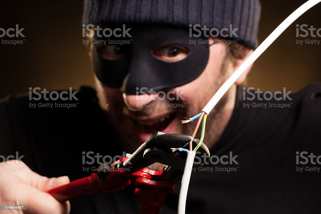 Thief Happily Cutting Electric Wire with Nippers royalty-free stock photo