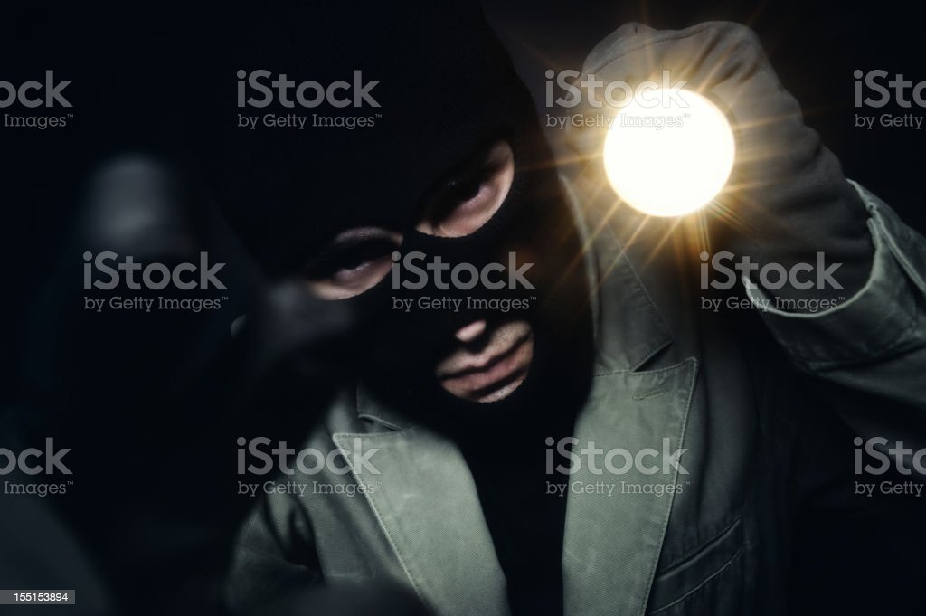 Thief holding a torch stock photo