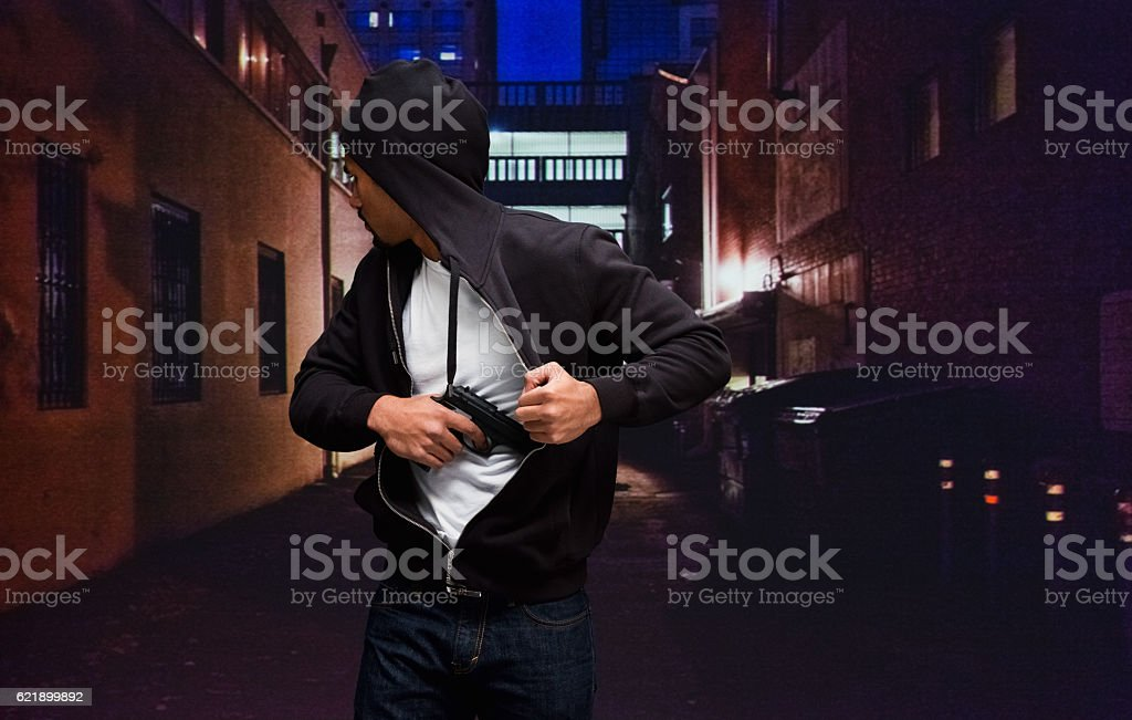 Thief in action with gun at night outdoors stock photo