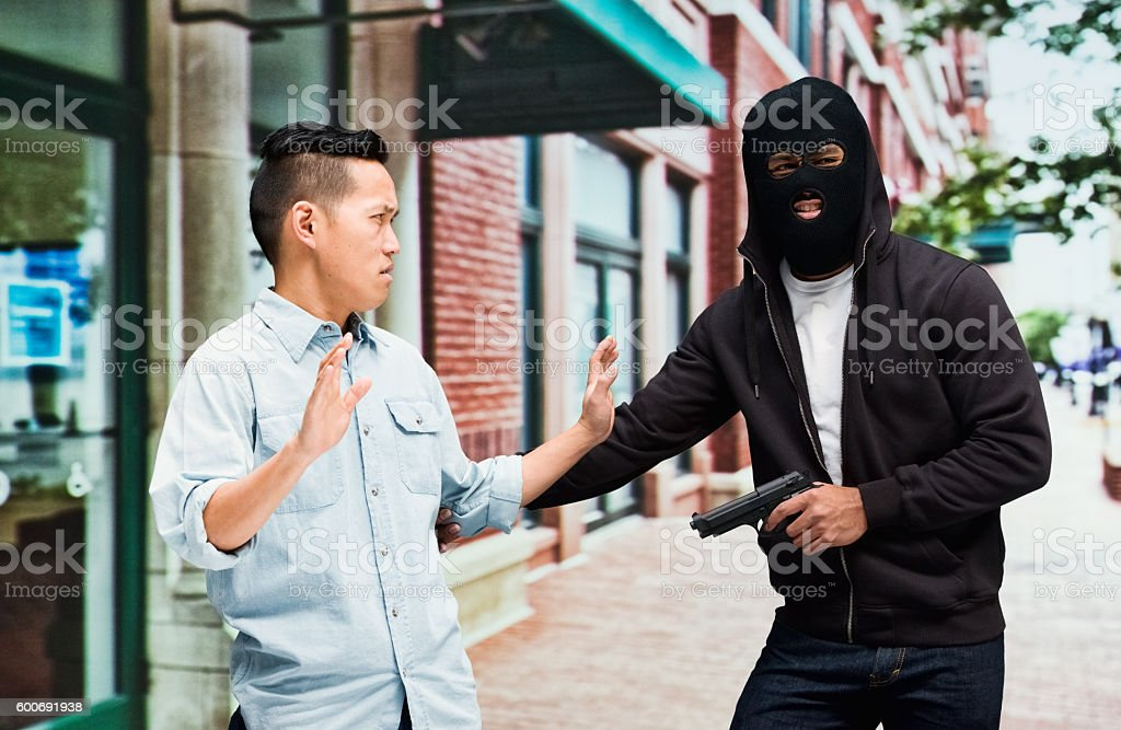 Thief in action with gun outdoors stock photo