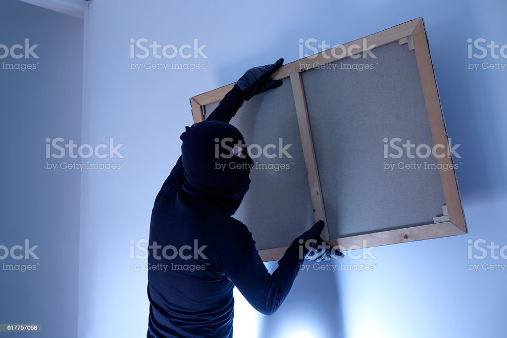 Thief inside home  stealing a painting from the wall stock photo