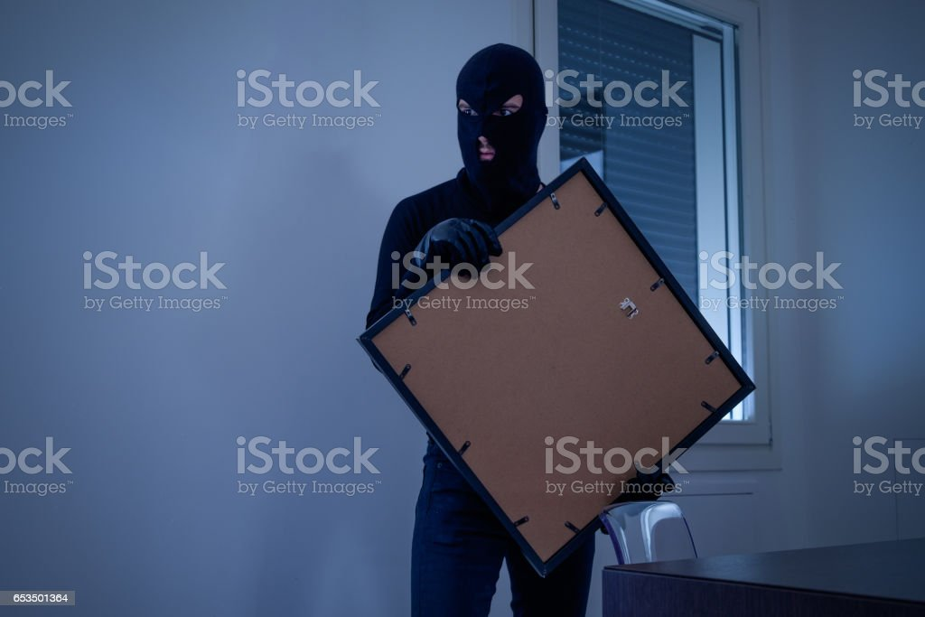 Thief inside home  stealing a painting stock photo