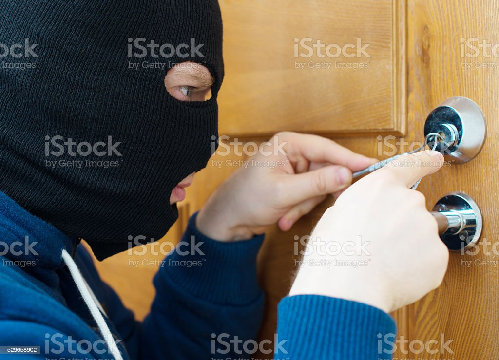 Thief opening door with lock picker. stock photo