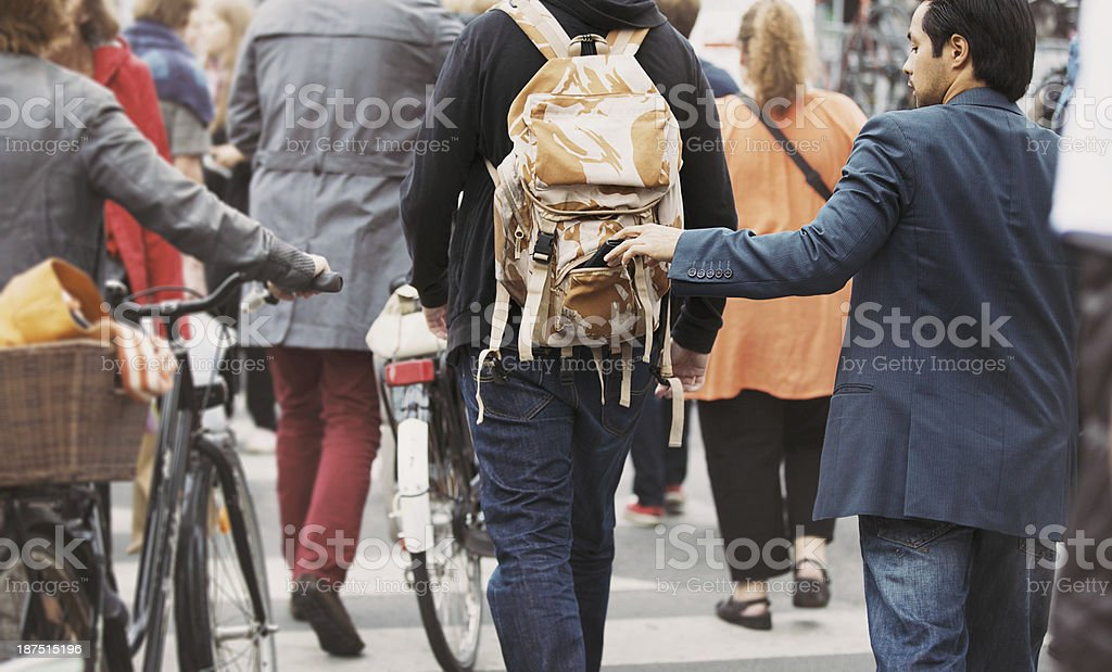Thief pulls wallet out of a man backpack stock photo