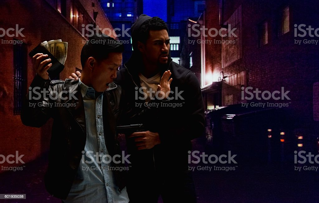 Thief staling from man with gun outdoors stock photo