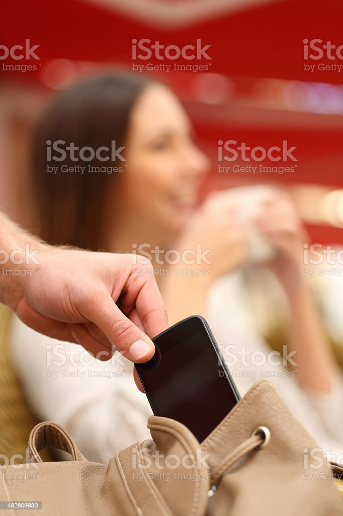 Thief stealing a mobile phone from a woman bag stock photo