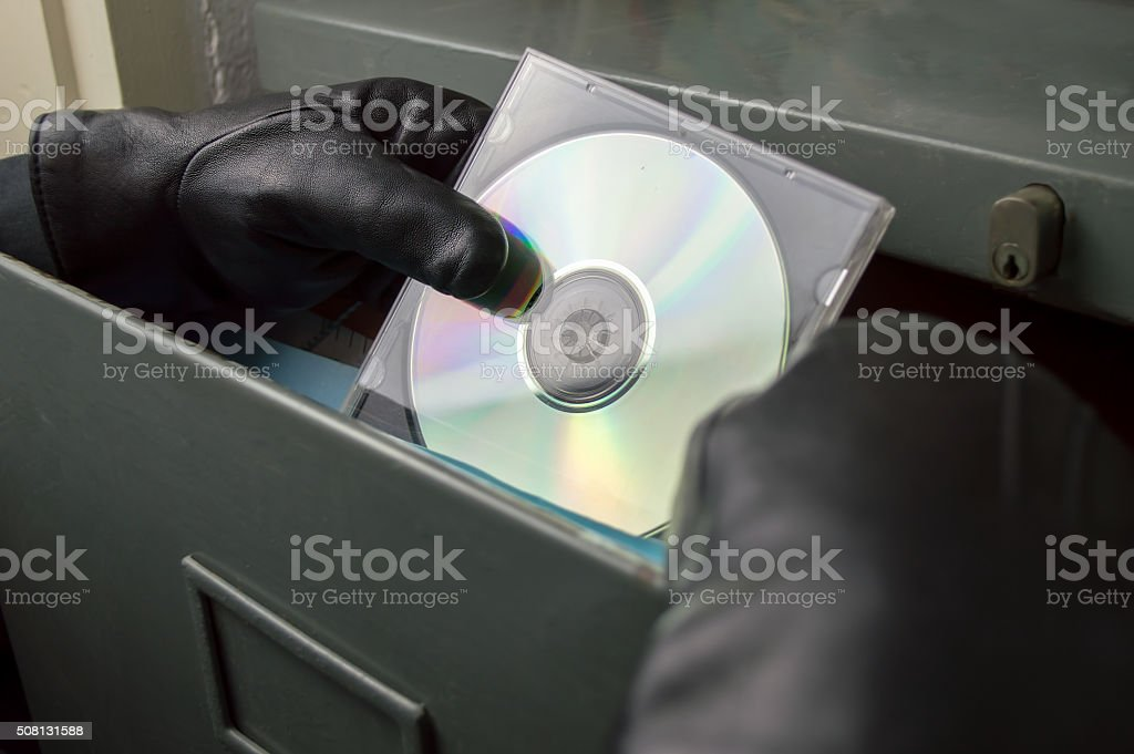 thief stealing documents in compact disc stock photo