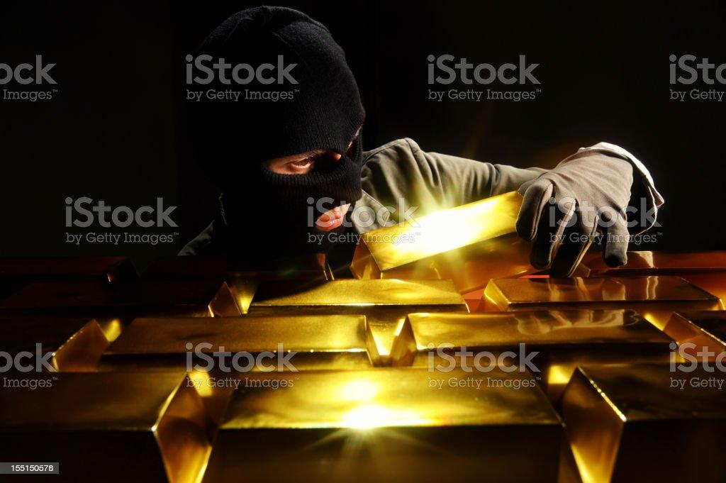 Thief stealing gold bars royalty-free stock photo