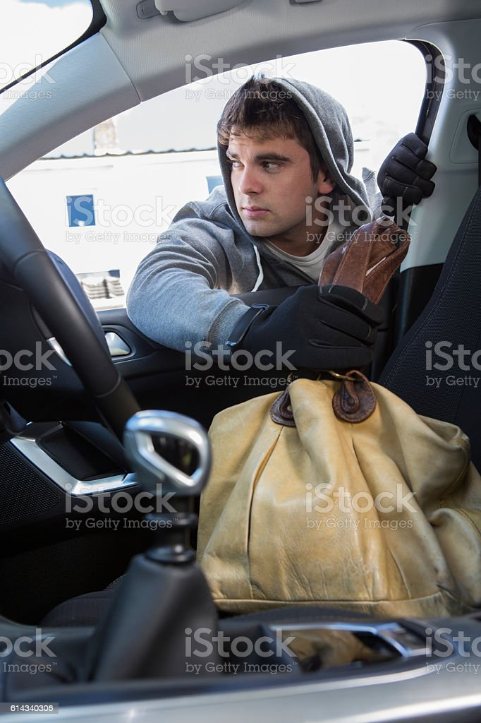 Thief Stealing Handbag From Car stock photo