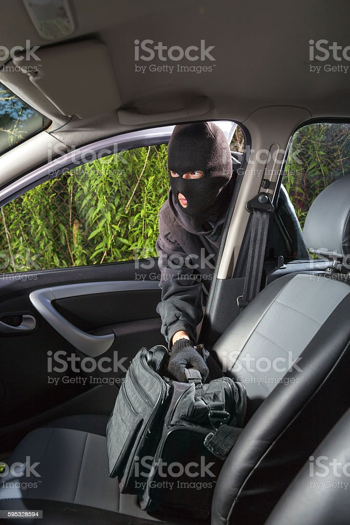Thief steals bag from the car stock photo