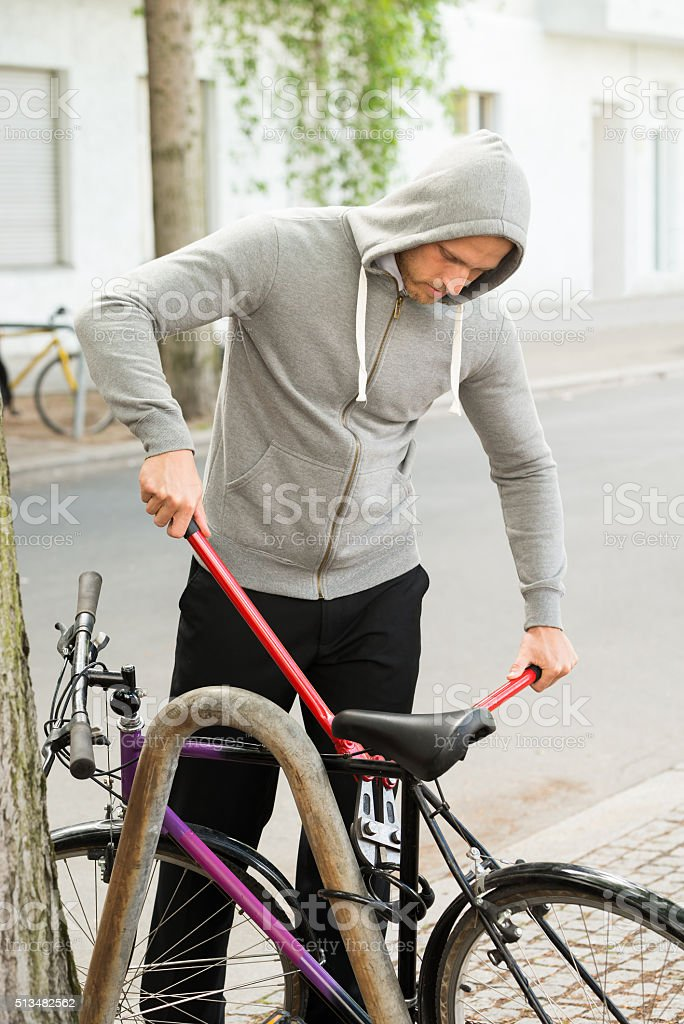 Thief Trying To Break The Bicycle Lock stock photo