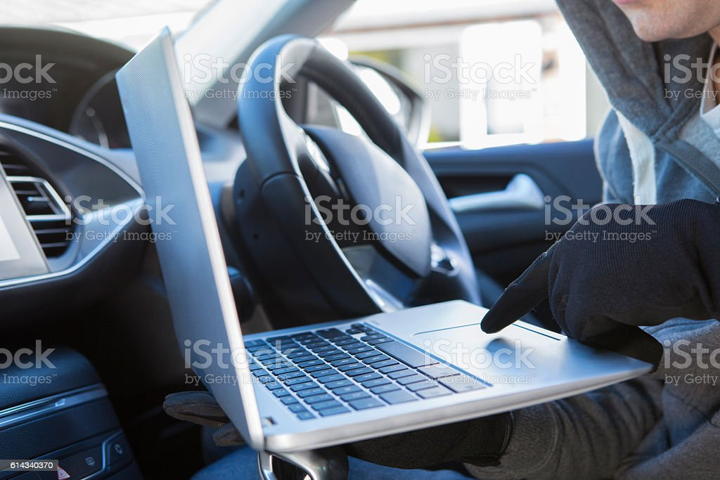 Thief Using Laptop To Hack Into Car Security Software stock photo