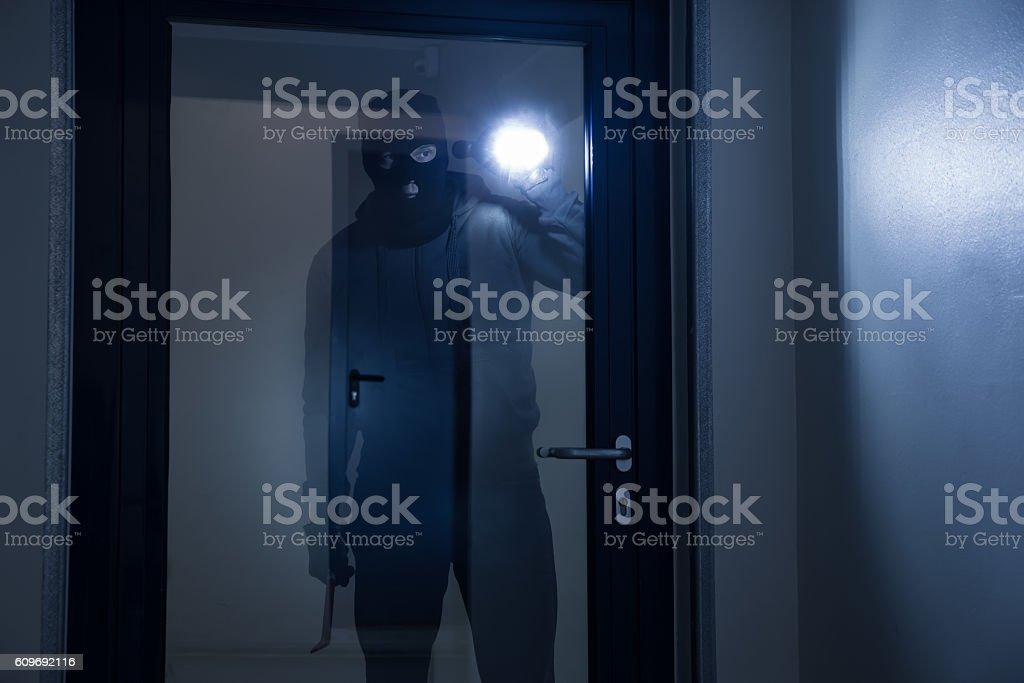 Thief With Flashlight Trying To Break Door stock photo