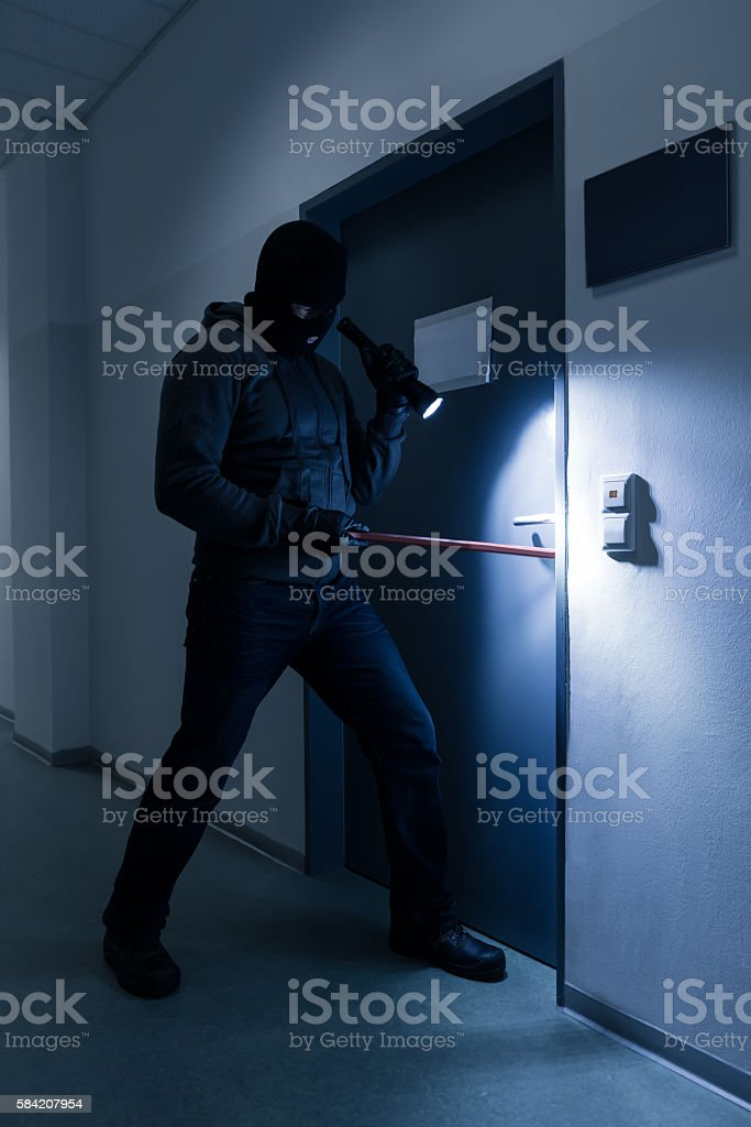 Thief With Flashlight Trying To Break Office Door stock photo