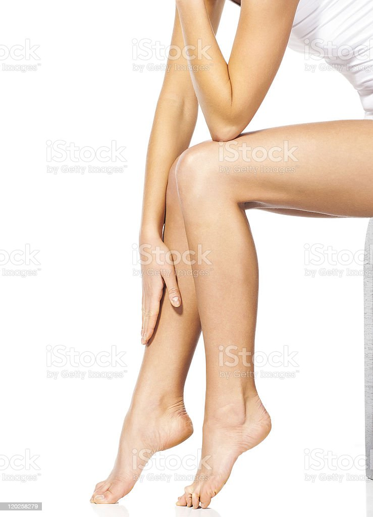 Thin and long feet of the beautiful sitting woman stock photo