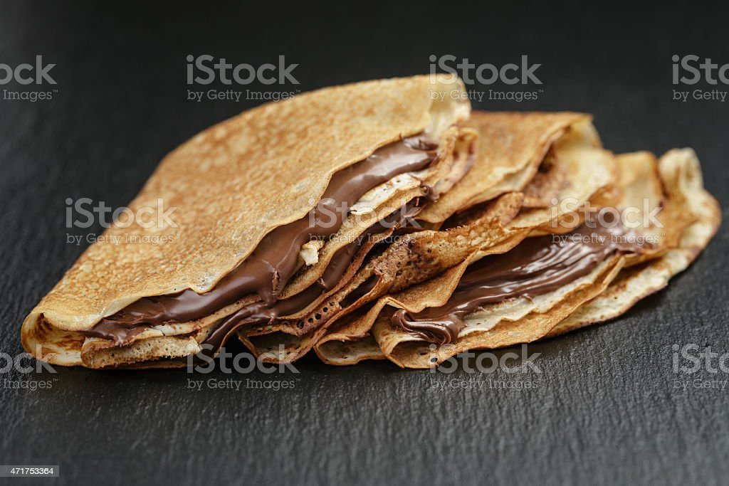 thin crepes or blinis with chocolate cream on slate board stock photo