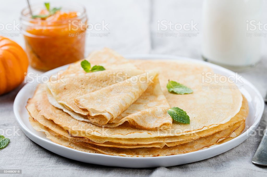 Thin crepes or pancakes with butter, honey and sour cream stock photo