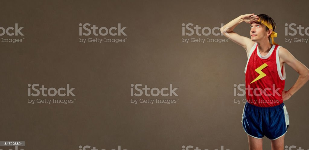 A thin funny guy in sports clothes looks stock photo