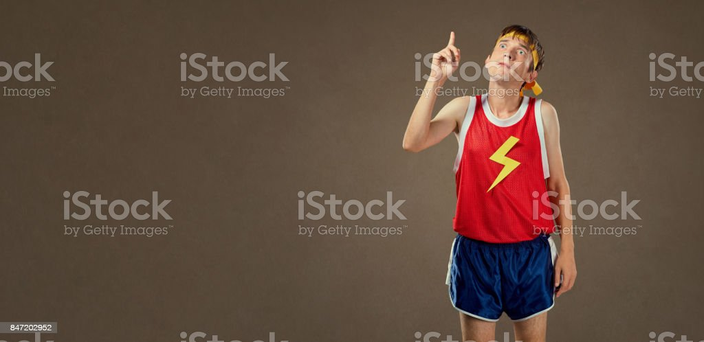 A thin funny guy in sports clothes shows his finger up. stock photo