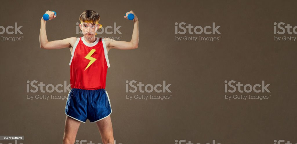 A thin funny guy in sports clothes with small dumbbells stock photo