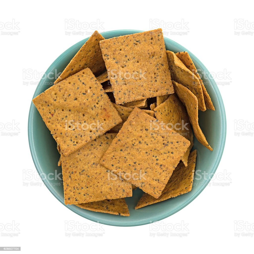 Thin gourmet snack crackers in a green bowl stock photo