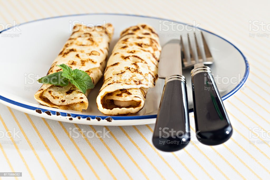 thin pancakes rolled crepes mint on a plate with knife stock photo