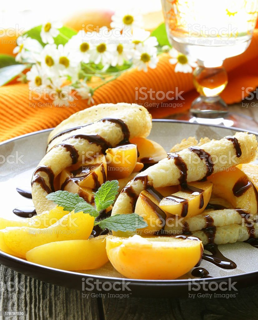 thin pancakes (crepes) with peaches and chocolate sauce royalty-free stock photo