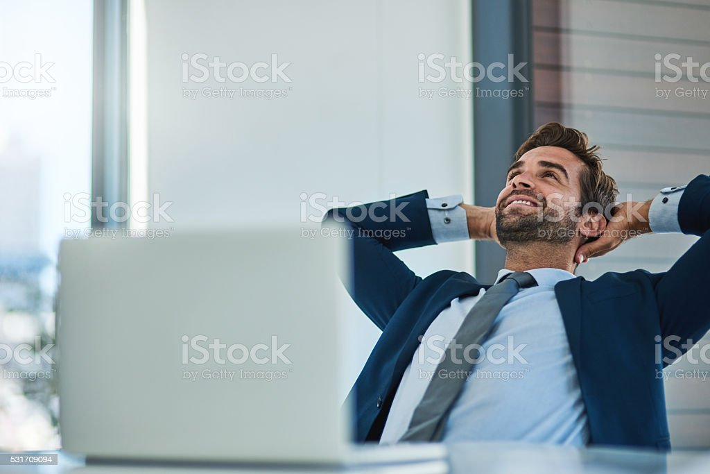Shot of a young corporate businessman taking a break at an office desk