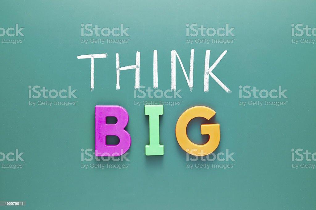 Think bigger concept, words on blackboard stock photo