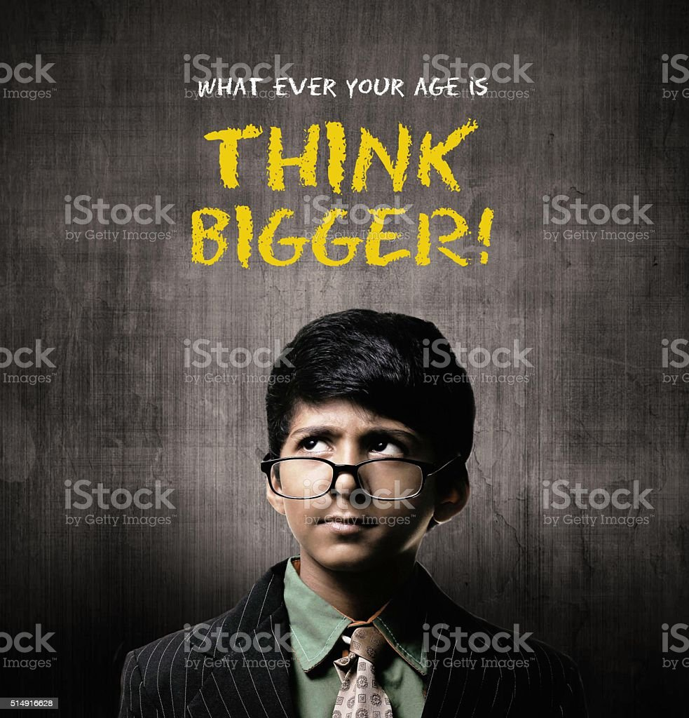 Think Bigger. Genius Little Boy Wearing Glasses, Thinking Near Chalkboard stock photo