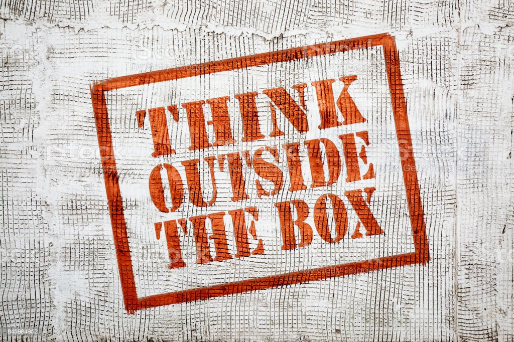 think outside the box graffiti on stucco wall stock photo