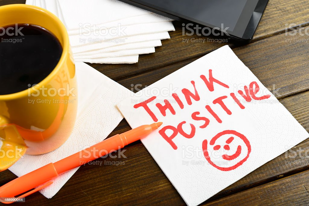 Think positive writing on white napkin stock photo