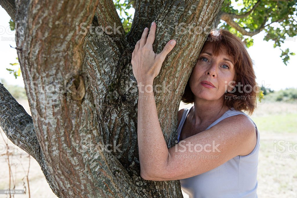 thinking aging woman touching a tree for reinsurance stock photo