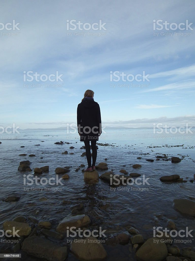 Thinking at the edge of the sea stock photo