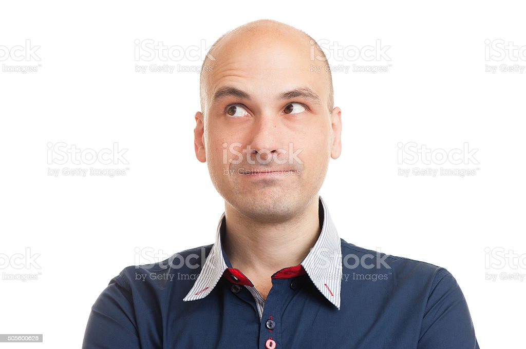 Thinking bald man looking up at copyspace stock photo