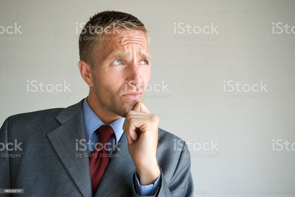 Thinking Businessman Looking with Furrowed Brow Hand on Chin royalty-free stock photo