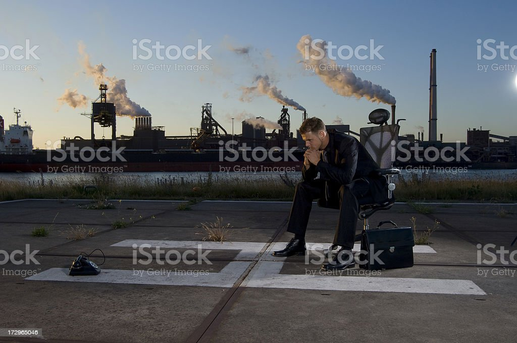 thinking businessman on helipad in industrial environment royalty-free stock photo