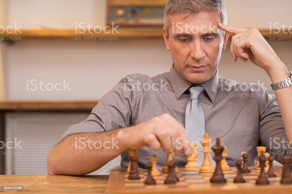 Thinking businessman playing chess stock photo