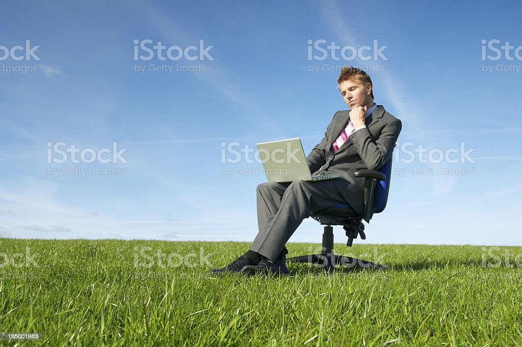 Thinking Businessman Sits Outdoors in Grass with Laptop royalty-free stock photo