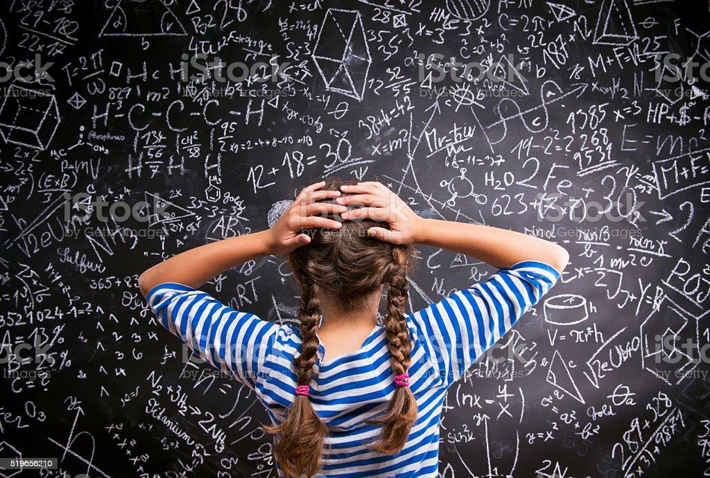 Thinking girl holding head against big blackboard, back view stock photo