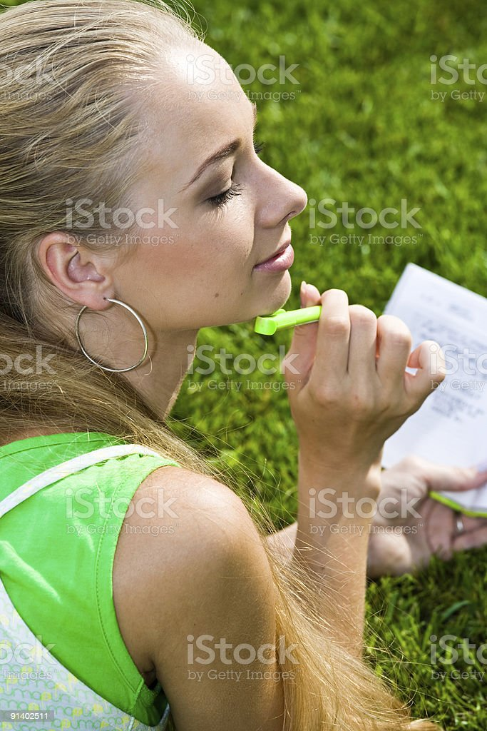Thinking girl on the grass stock photo