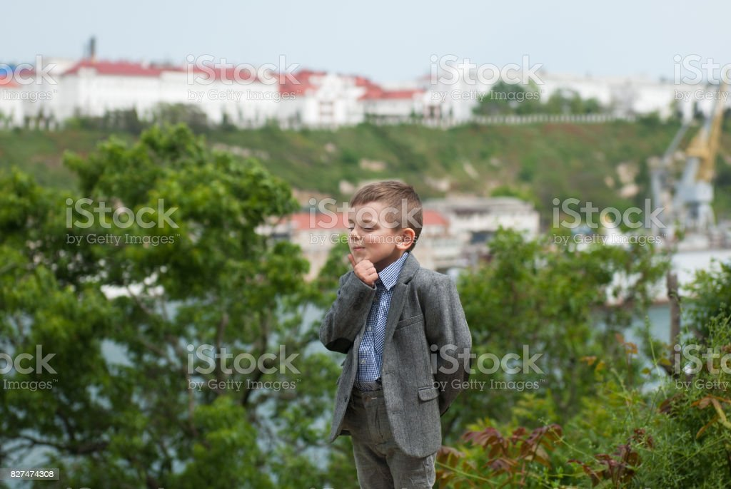 Thinking little boy in a jacket against the backdrop of a sea, trees and an old city stock photo