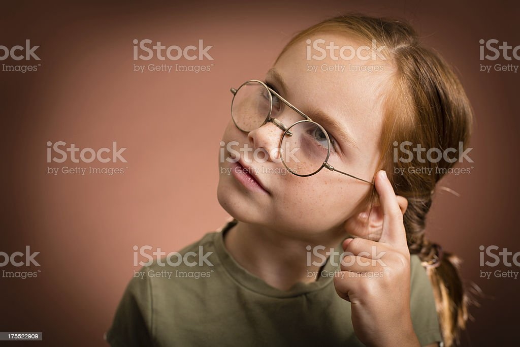 Thinking Little Girl Wearing Vintage Nerdy Glasses royalty-free stock photo