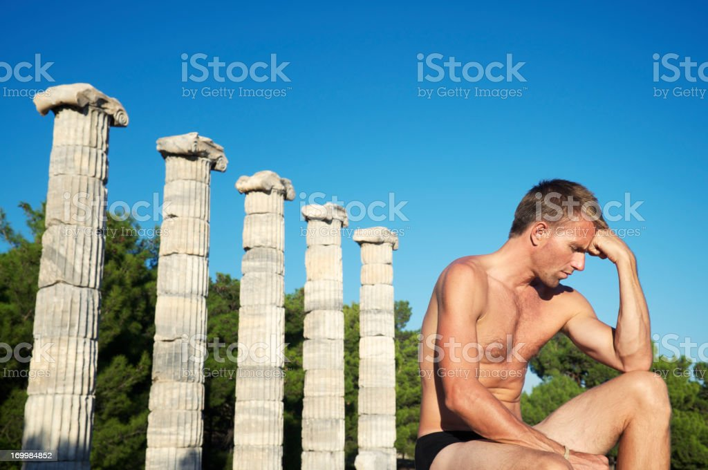 Thinking Man Sits Next to Row of Ancient Columns stock photo