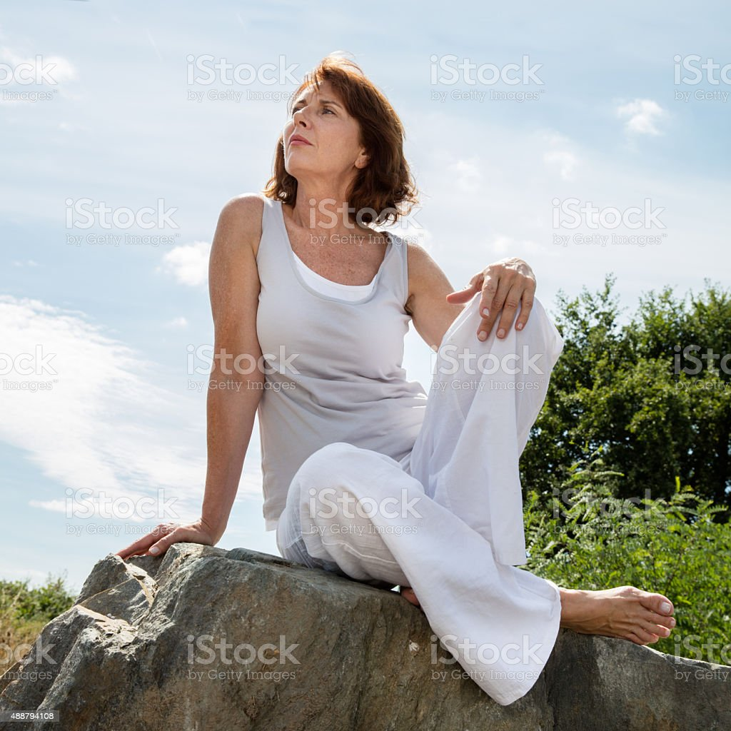 thinking mature yoga woman relaxing outdoors stock photo