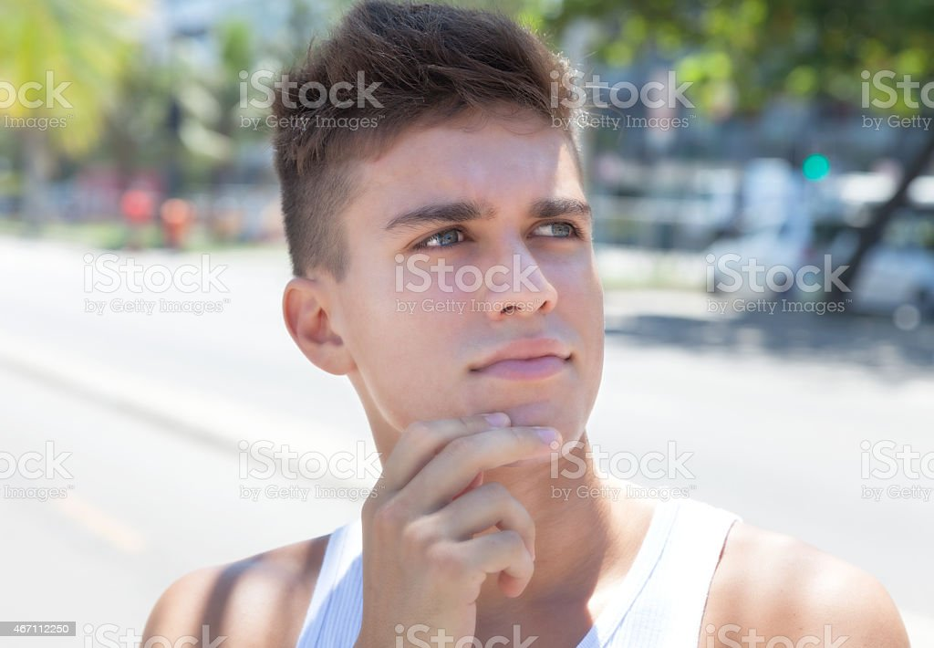 Thinking muscular guy in the city stock photo