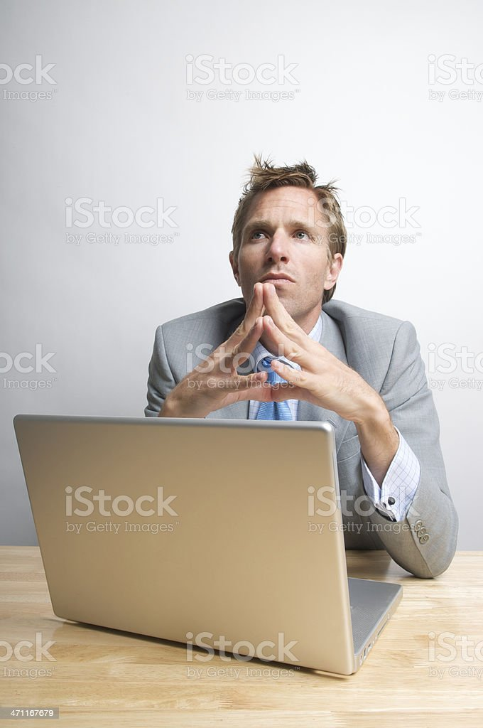 Thinking Office Worker Businessman Holds Fingertips Together Laptop at Desk royalty-free stock photo
