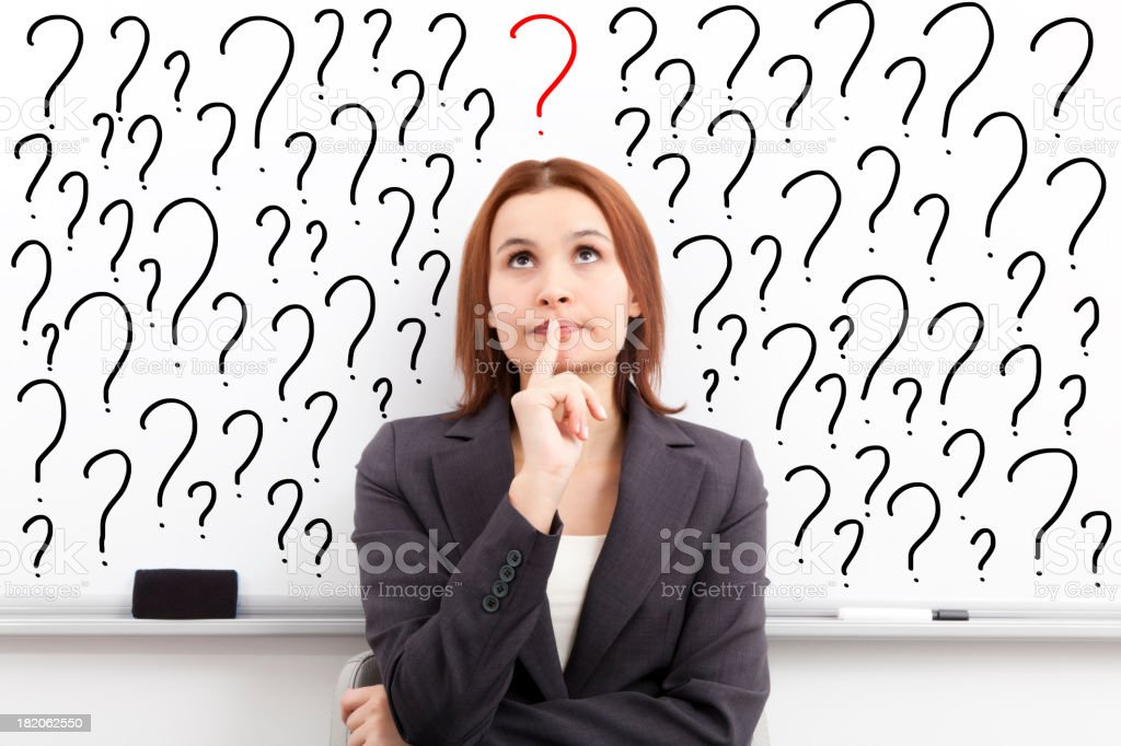 thinking woman in front of question marks written whiteboard stock photo